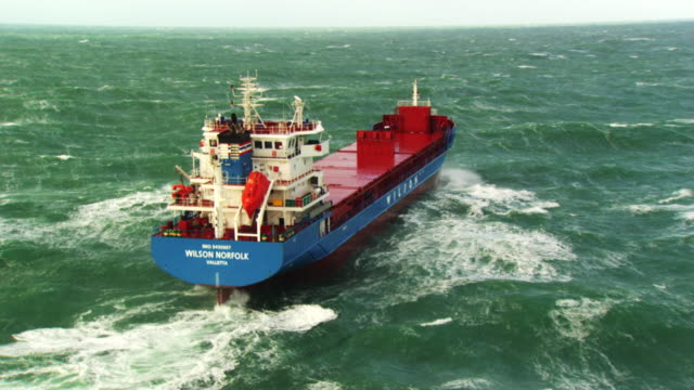vídeos de stock e filmes b-roll de france, bretagne: cargo boat cleaving through waves - navio cargueiro