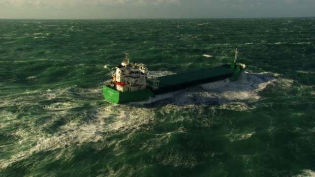 france, bretagne: cargo boat cleaving through waves - bretagna video stock e b–roll