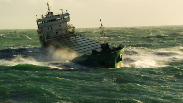 vídeos de stock e filmes b-roll de france, bretagne: cargo boat cleaving through waves - barco