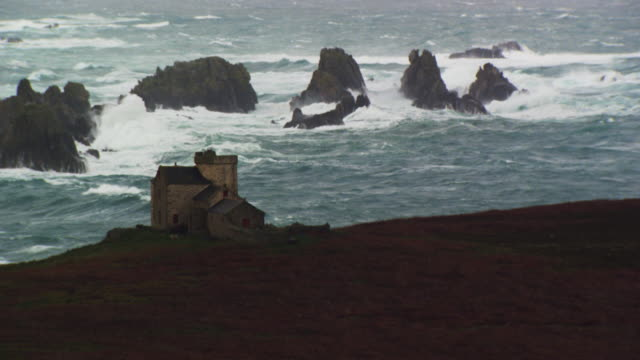france, bretagne: stone house with coastal rocks hit by waves - ブルターニュ点の映像素材/bロール