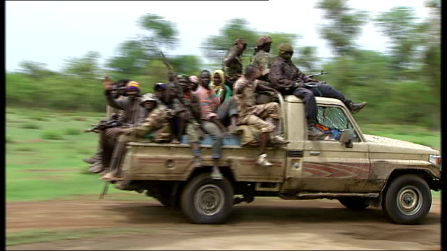 France hosts talks to help Darfur Rebel fighters holding weapons sat aboard truck as along Rebels holding rifles along thru forest area an on back of...