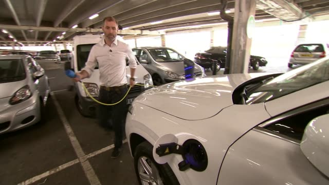 stockvideo's en b-roll-footage met france joins movement away from petrol and diesel powered cars england london int various of hybrid volvo car being droven into parking space in car... - hybride voertuig