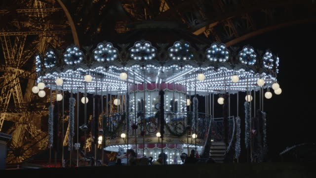 france - paris : carousel near to the eiffel tower at night - 回転遊具点の映像素材/bロール