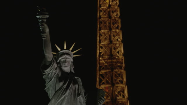 france - paris : eiffel tower and statue of liberty at night - île de france stock-videos und b-roll-filmmaterial