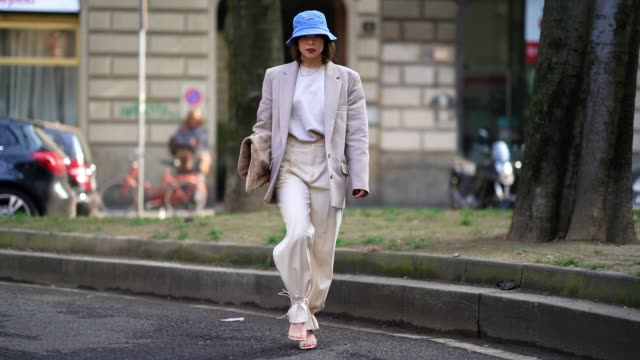 francesca cina wears a blue bob hat, a gray oversized blazer jacket, a white t-shirt, white pants, a bag, shoes, outside calcaterra, during milan... - gray jacket stock videos & royalty-free footage