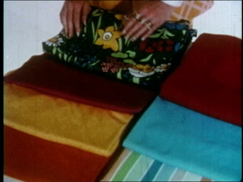 stockvideo's en b-roll-footage met francine coffey fashion director of the singer company displays various trevira polyester knit fabrics / she holds up sewing pattern envelope / she... - polyester