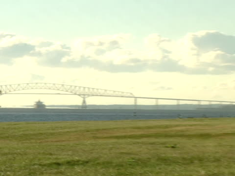 francis scott key bridge over the baltimore harbor crossing the patapsco river w/ grass in fg pan country side to ws of fort mchenry - hafen von baltimore stock-videos und b-roll-filmmaterial