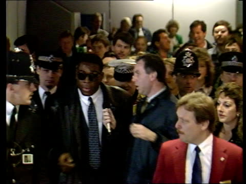 a england london heathrow frank bruno and girlfriend laura mooney seated on back of buggy as along thru customs hall away track forward tms police as... - cordon boundary stock videos & royalty-free footage