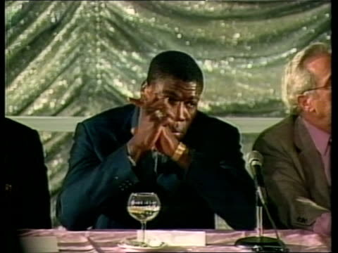 frank bruno v mike tyson fight preview:; a) usa: las vegas: hilton hotel: frank bruno shakes man wearing traditional african dress and takes seat at... - 女子ボクシング点の映像素材/bロール