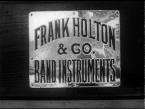 vidéos et rushes de frank holton and company building cu 'frank holton co band instruments' plaque women workers cleaning saxophones at table mr walters testing trumpet... - 1952
