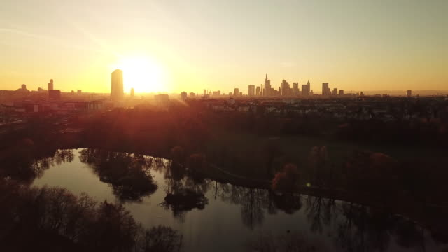 Frankfurt am Main - Aerial at sunset - Flight over a small lake, Skyline in the background