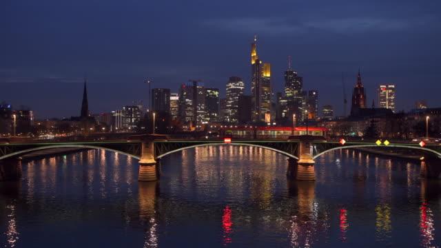 frankfurt skyline illuminated at dusk twilight. - uferviertel stock-videos und b-roll-filmmaterial