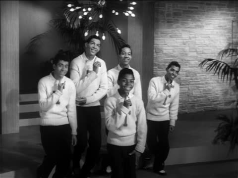 Frankie Lymon Teenagers near small stage bowing to applause from offscreen audience