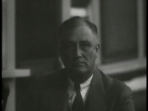 Franklin Delano roosevelt sitting in chair in room looking very serious at camera in heavy shadow left No other people