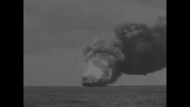 USS Franklin on Pacific Ocean with fire raging and black smoke billowing from explosions / ship with smoke rising / billowing smoke surrounds ship...