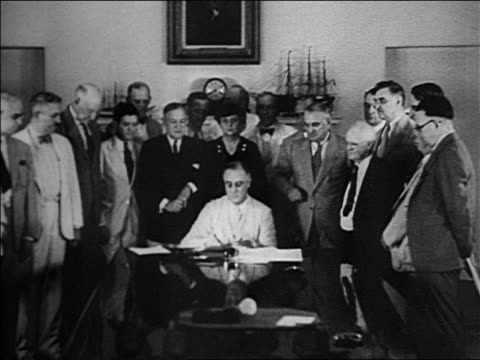 vídeos de stock, filmes e b-roll de franklin roosevelt signing papers at table with crowd of people standing behind him - 1933