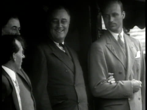 vídeos de stock e filmes b-roll de franklin roosevelt standing w/ assistant at train entrance, reporting asking 'when are you coming back?' fdr answering 'just as soon as congress will... - 1933