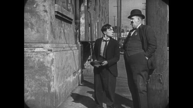 1921 Frantic man (Buster Keaton) collides with tall angry policeman who then follows him through the streets