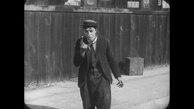 1921 frantic man (buster keaton) searches street for horseshoe before obliviously throwing it at shocked policeman - 1921年点の映像素材/bロール