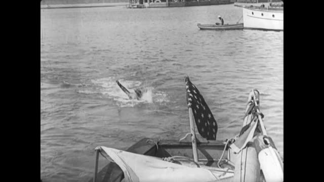 1921 frantic man (buster keaton) swims back to his boat to join wife (sybil seely) and child - 1921年点の映像素材/bロール