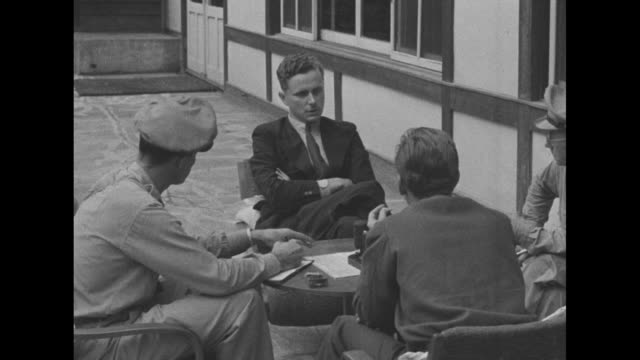 of franz josef spahn, former nazi party leader in japan, seated at a table with lt breakstone, don bell and another man; he is sharply questioned by... - ゲシュタポ点の映像素材/bロール