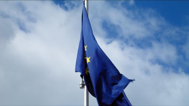 frayed European Union flag blows in cloudy sky