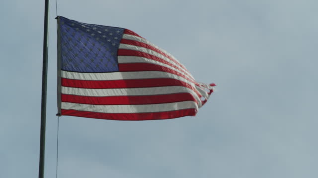 frayed, worn and ragged united states flag waves in slow motion from a flag pole - ausgefranst stock-videos und b-roll-filmmaterial