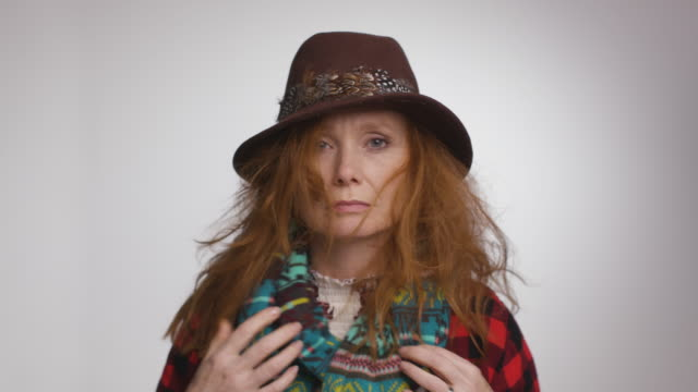 frazzled woman puts on hat in mirror - scarf stock videos & royalty-free footage