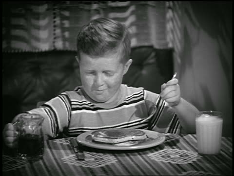 B/W 1941 freckled boy pouring syrup + cutting pancakes / industrial