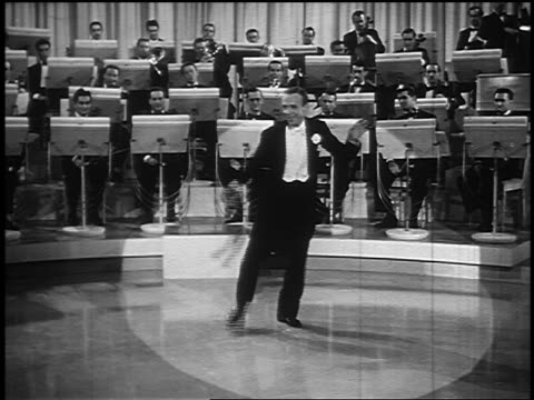 fred astaire in tails with wand tap dancing in spotlight / orchestra in background - tap dancing stock videos & royalty-free footage