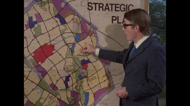 fred lloyd roach, general manager of the milton keanes development society, stands before a map of milton keynes and talks about it's design, with... - construction industry stock videos & royalty-free footage