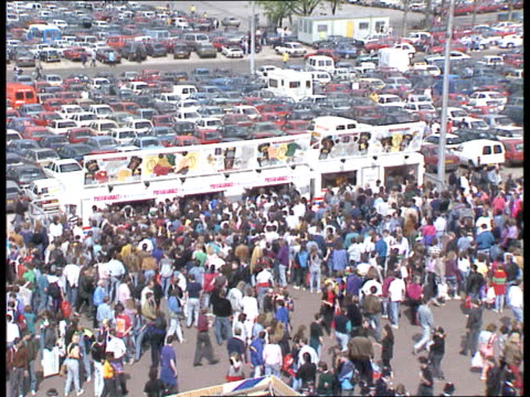 freddie mercury tribute concert; england london wembley stadium tgv people along concourse and queueing at merchandise stall with car park in b/g gv... - gedenkveranstaltung stock-videos und b-roll-filmmaterial