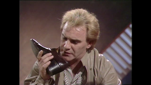 freddie starr talks into a shoe and receives a 'response' back demonstrating his ability to throw his voice. - comedian stock videos & royalty-free footage