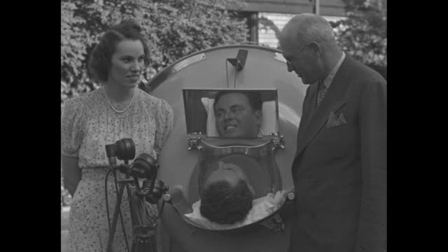 stockvideo's en b-roll-footage met frederick snite, jr. in an iron lung, his new wife, teresa, and father, frederick snite, sr., standing next to him outside their home in river... - polio