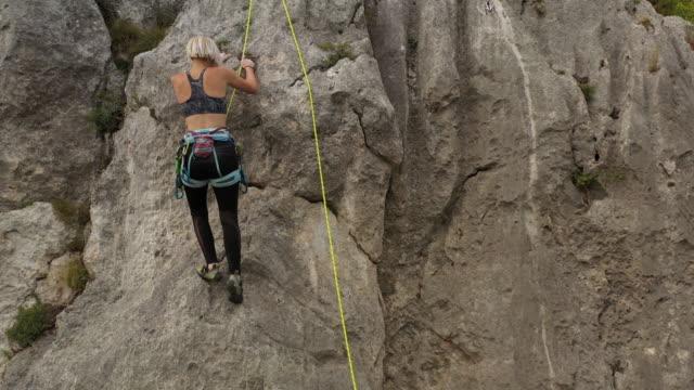 vídeos y material grabado en eventos de stock de escalador libre que llega a la cima de la roca - escalada libre
