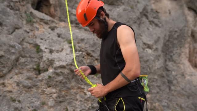 stockvideo's en b-roll-footage met vrije klimmer die de touwen vaststelt alvorens rots te beklimmen - free climbing