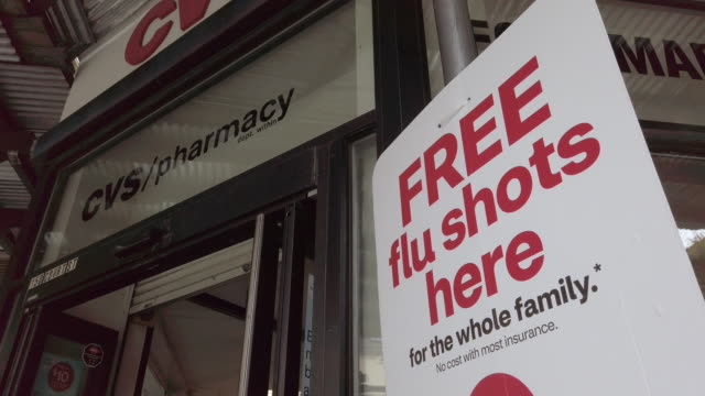 """free flu shot here"" sign in front of a cvs pharmacy entrance. - cvs caremark stock videos & royalty-free footage"