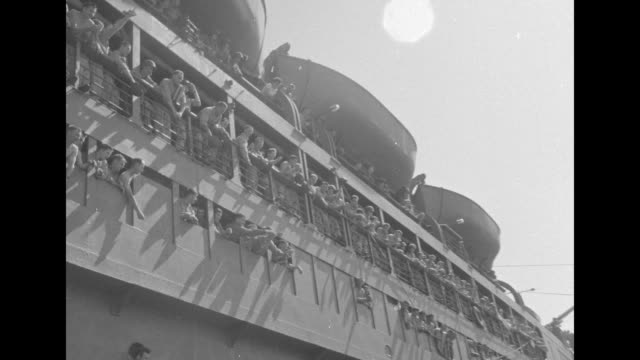 vídeos de stock, filmes e b-roll de free french cruiser sails past us troop transport heading towards australian port / sailor on board us ship signals with flags / shot from ship as it... - general macarthur