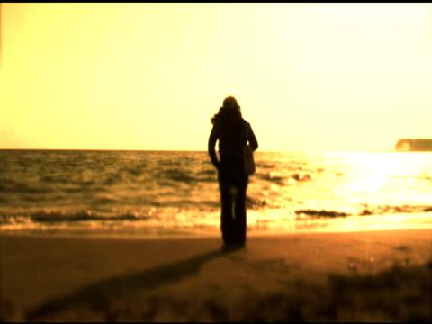 フリースタンド式の独立した女性は海に黄色の夕日 - 見つめる点の映像素材/bロール