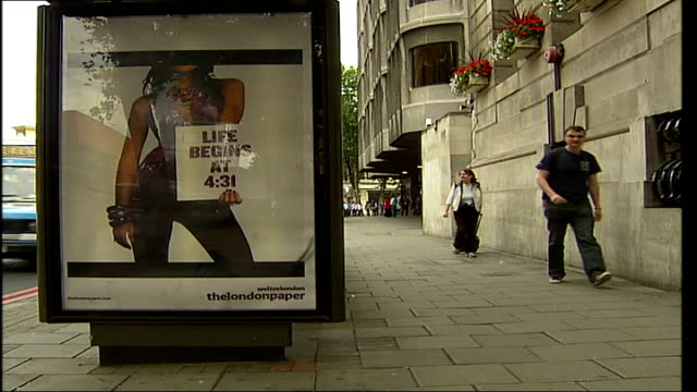 free london newspapers face competition ext poster advertisement for 'the london paper' on bus stop as people along close up 'we live london the... - bushaltestelle stock-videos und b-roll-filmmaterial