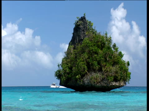 Free standing rock covered in trees speed boat emerges and travels across turquoise water Palau