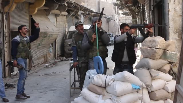 vídeos de stock, filmes e b-roll de free syrian army fighters fire at the front line and other move towards it in aleppo syria - batalha guerra