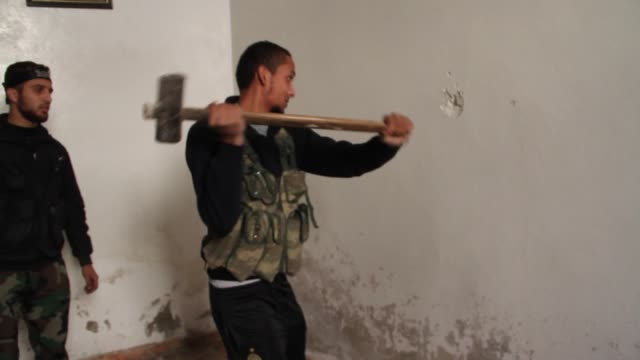 free syrian army fighters make a hole in a wall near the frontline in aleppo syria - sledgehammer stock videos & royalty-free footage