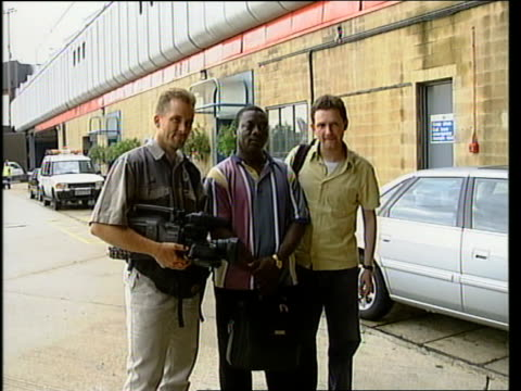 Freed journalists return from Liberia ITN London Heathrow Airport EXT Journalists Tim Lambon Sorious Samura and David Barrie posing for photocall...