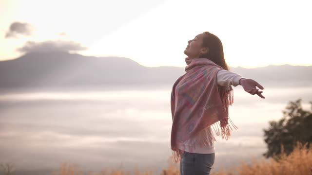 freedom asian woman woman standing and opening arms raised on top of mountain, enjoying view at sunset - east asia stock videos & royalty-free footage