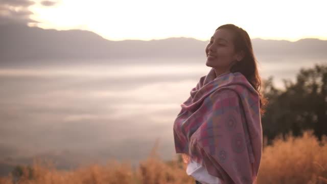 自由アジアの女性山の上に立って、夕暮れ時の眺めを楽しむ女性 - 高い点の映像素材/bロール