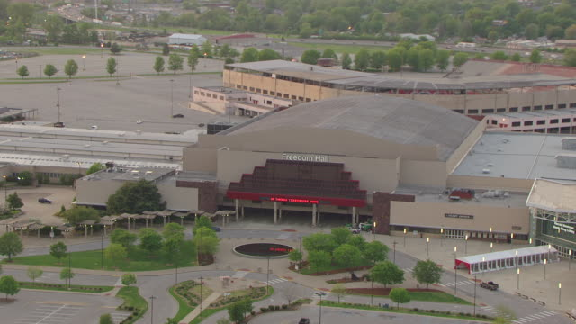 MS AERIAL PAN Freedom Hall entrance and pull out to reveal downtown skyline in background / Louisville, Kentucky, United States