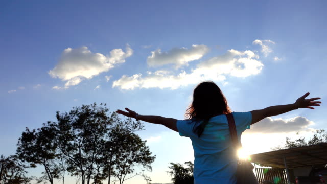 Freedom of Woman with arm raised at sunset.