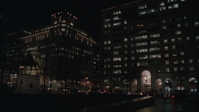pan freedom plaza at night, with city lights and traffic headlights / washington, d.c., united states - freedom plaza video stock e b–roll