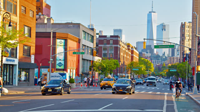 freedom tower and financial district from residential part of town with small stores. urban road and cars. - tall high stock videos & royalty-free footage